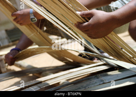 Karen Paduang refugees from Burma (Myanmar) are making a thatched roof in Ban Nai Soi, Thailand. - Stock Photo