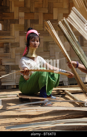 Karen Paduang longneck refugees from Burma (Myanmar) are making a thatched roof in Ban Nai Soi, Thailand. - Stock Photo
