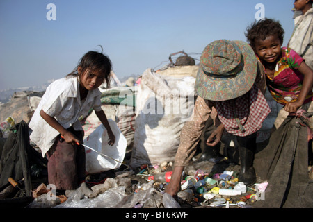 Boy and girl child laborers are searching for recyclable plastic bags in a garbage dump in Phnom Penh, Cambodia. - Stock Photo