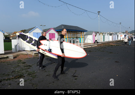 Surfers arriving at Paignton beach in Devon - Stock Photo