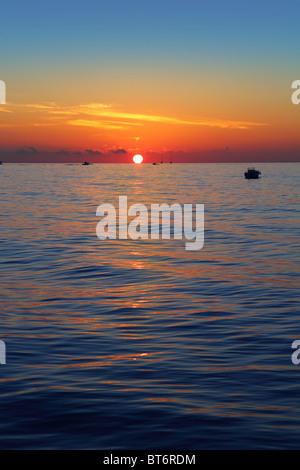 seascape sunrise first sun orange in blue sea ocean - Stock Photo