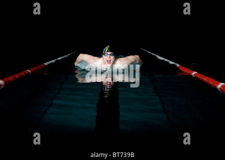 Professional swimmer taking breath during butterfly swimming - Stock Photo