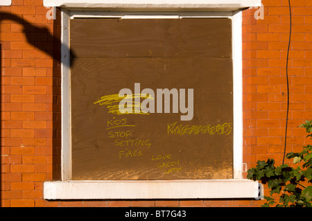 Message written on a boarded up derelict terraced housing awaiting demolition in the Clayton district of Manchester, - Stock Photo