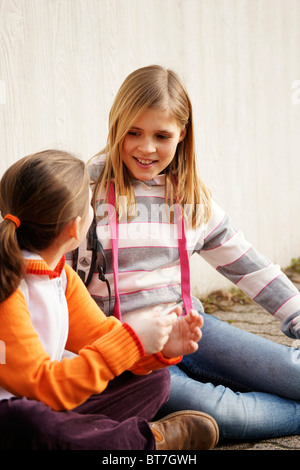 Two girls talking in the schoolyard - Stock Photo