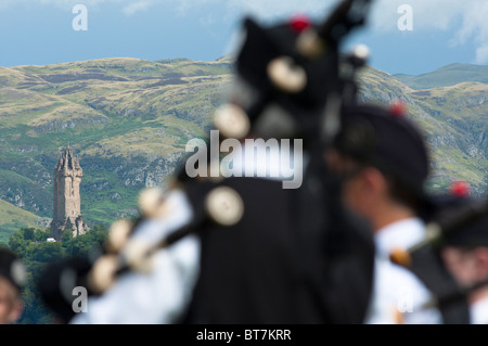Pipers play at Stirling castle with the Wallace Monument seen in the distance. Scotland. - Stock Photo