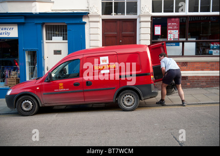 A postman loading a sack of mail into his van UK - Stock Photo