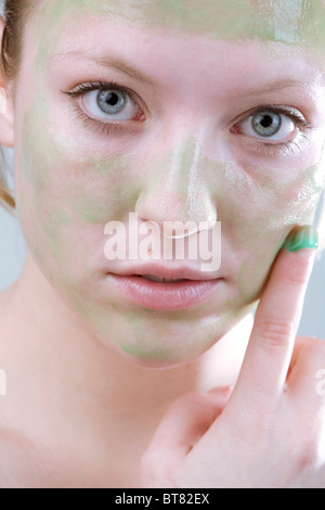 Young woman applying a peel-off mask - Stock Photo