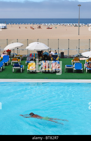 Man swims by a group of people sunbathing next to an outdoor swimming pool in front of the Figueira da Foz beach - Stock Photo