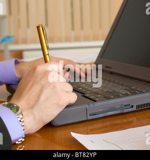 The laptop and man's hands with a pen - Stock Photo