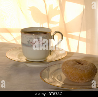 A sunny morning with coffee and donut for breakfast, with a bird on the tree outside the window. - Stock Photo