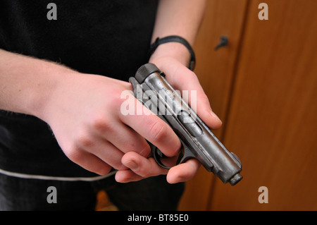 Juvenile holding a pistol - Stock Photo