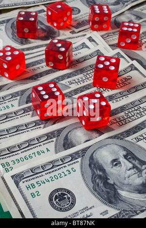 One hundred dollar bills and red dice - Stock Photo