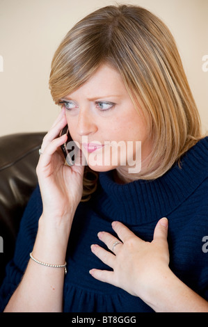 Young woman chatting on her mobile phone and looking angry and upset. - Stock Photo