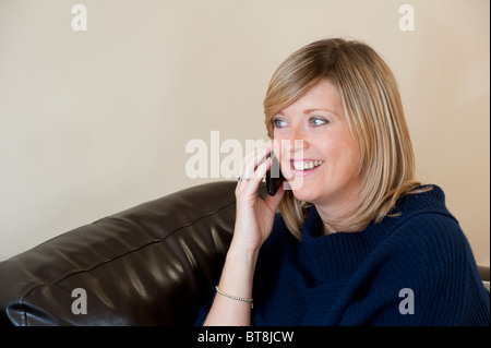 Young woman chatting on her mobile phone and looking happy. - Stock Photo