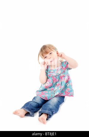 female toddler pulling faces at camera on isolated white background - Stock Photo