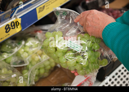 Woman choosing a packet of cheap priced grapes in a plastic bag displayed on a Lidl supermarket shelf. UK Britain - Stock Photo