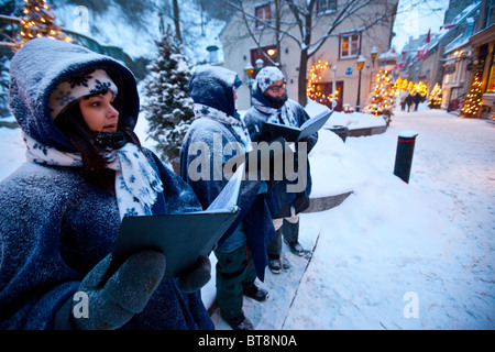 Christmas carolers on Rue du Petit Champlain in lower Old Quebec City, Canada - Stock Photo