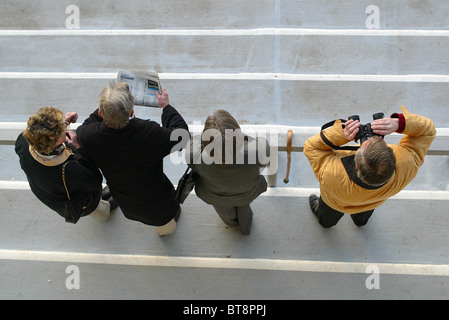 Race goers at Lingfield Park Race course watch the action from the grandstand.  Picture by James Boardman. - Stock Photo