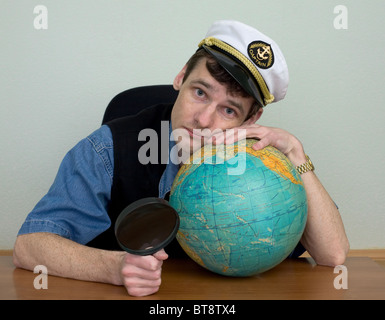 Guy in a sea cap with a terrestrial globe - Stock Photo