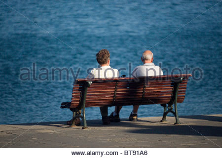 Elderly couple sitting on a wooden bench looking at the sea - Stock Photo