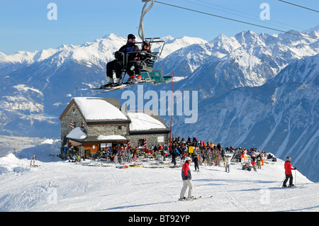 Skiers sitting on a chair lift hovering above the refuge Les Violettes in the Pennine Alps, Crans Montana, Valais, - Stock Photo