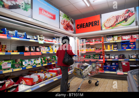 A woman shopping for bargain foods in Lidl discount supermarket UK - Stock Photo