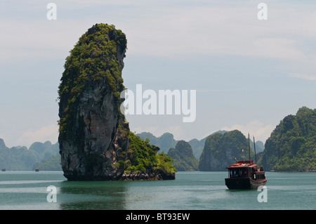 Limestone Karst and Junk in Halong Bay, Vietnam - Stock Photo