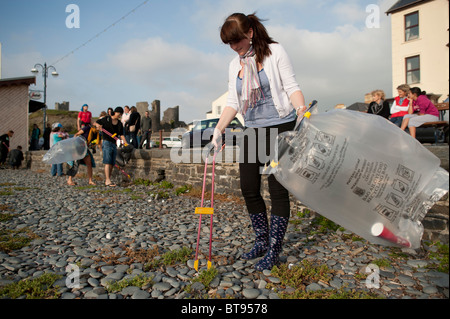 A group of Aberystwyth University 'coast care group' student volunteers picking up litter off the beach, Wales UK - Stock Photo