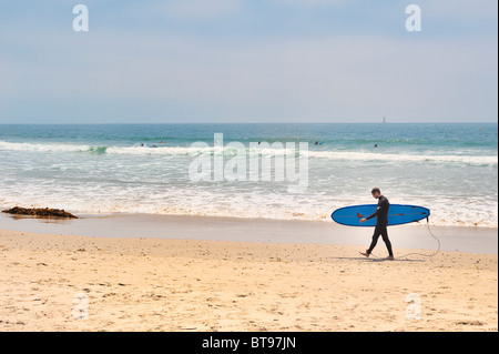Surfing USA : Male surfer profile view walks on Venice Beach, Los Angeles, California, wearing wetsuit carrying - Stock Photo
