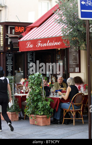 People relaxing and eating at La Fontaine restaurant in Paris, France - Stock Photo