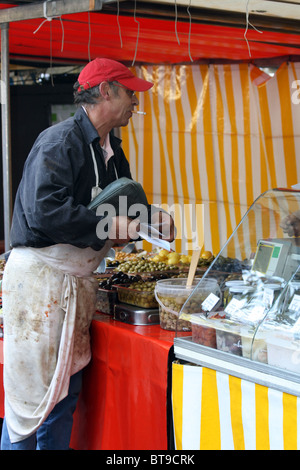 Man at a market stall selling olives in Paris, France - Stock Photo