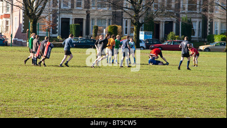 College rugby players practising tackling and passing on Roath Park recreation ground Cardiff UK GB - Stock Photo