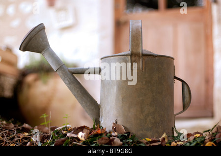 A metal watering can, outdoors - Stock Photo