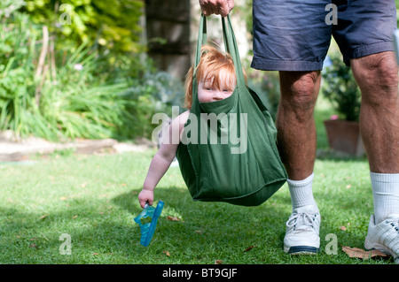 A senior man carrying a small child in a bag - Stock Photo