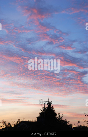 Sunset and cirrus clouds over rooftops in Anglesey, North Wales - Stock Photo