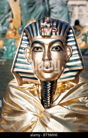 head & shoulders of living statue mime standing in Place de la Concorde Paris wearing gilded King Tut or Sphinx - Stock Photo