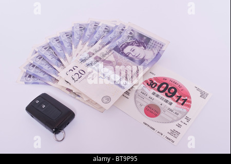 A car tax disc vehicle license with £200 in cash and car keys on a white background - Stock Photo