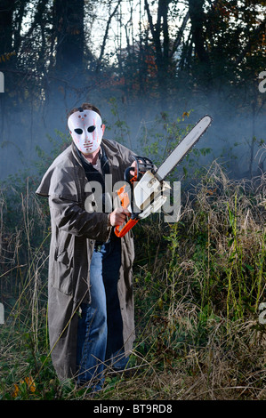Psychopathic scary man with mask and a chainsaw in a misty forest at dusk in the Fall at Halloween - Stock Photo