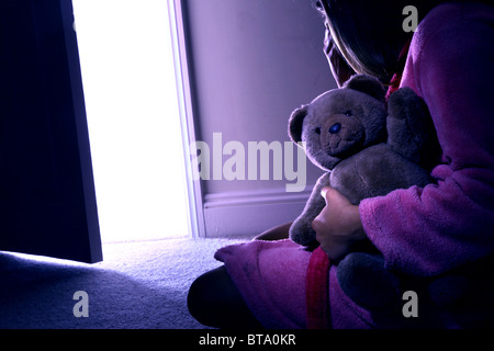 Young girl sitting holding a teddy bear, back view. Mod rel - Stock Photo