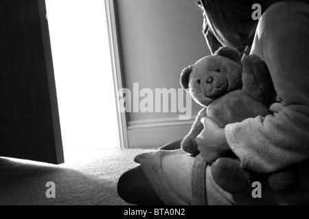 Young girl sitting holding a teddy bear, back view. - Stock Photo