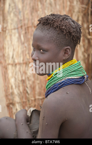 Nyangatom (Bumi) girl with piles of beads in front of her hut, Omo river Valley, Ethiopia - Stock Photo