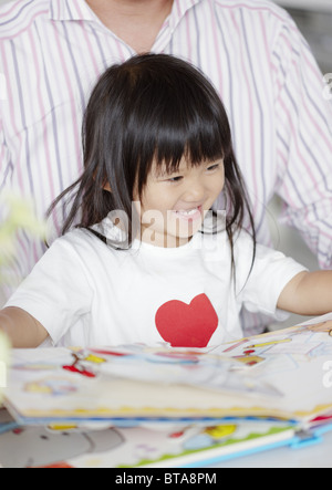 Father and daughter reading a picture book - Stock Photo