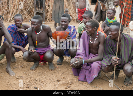 Nyangatom (Bumi) men sharing a calabash of cow blood, Omo river valley, Ethiopia - Stock Photo
