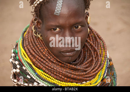 Nyangatom (Bumi) woman with piles of beads in her village, Omo river Valley, Ethiopia - Stock Photo