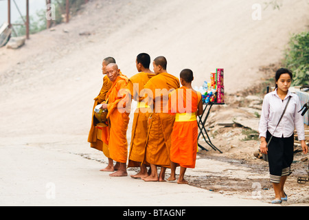 A curious elder monk takes a look at a passerby during his morning Alsm ceremony - Stock Photo