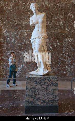 Venus de Milo or Aphrodite of Milos Statue and visitor Louvre Museum Paris, side view - Stock Photo