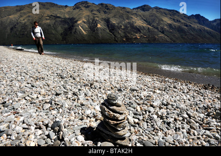 Woman walks on the stony beach of Lake Wakatipu, near Queenstown, New Zealand. The lake has views of nearby mountains. - Stock Photo
