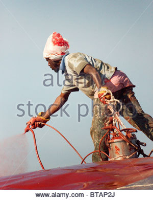 African migrant  worker spraying red paint wearing a plastic bag on his head to keep paint off his hair - Stock Photo