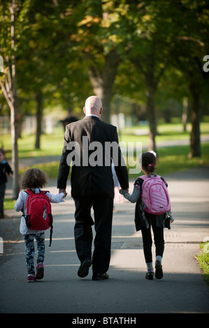 Rear view of a father walking hand in hand with his two small daughters on their way home from primary school, UK - Stock Photo