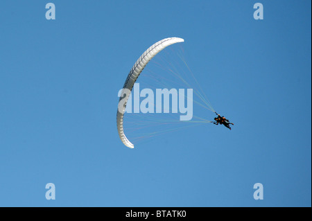 Two men tandem Paraglide with blue sky in background - Stock Photo